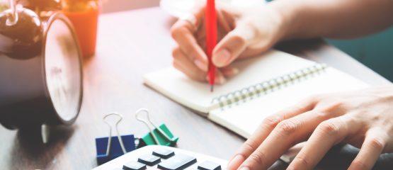imagem de uma pessoa utilizando um caderno e uma calculadora para representar a prestação de contas de uma campanha eleitoral