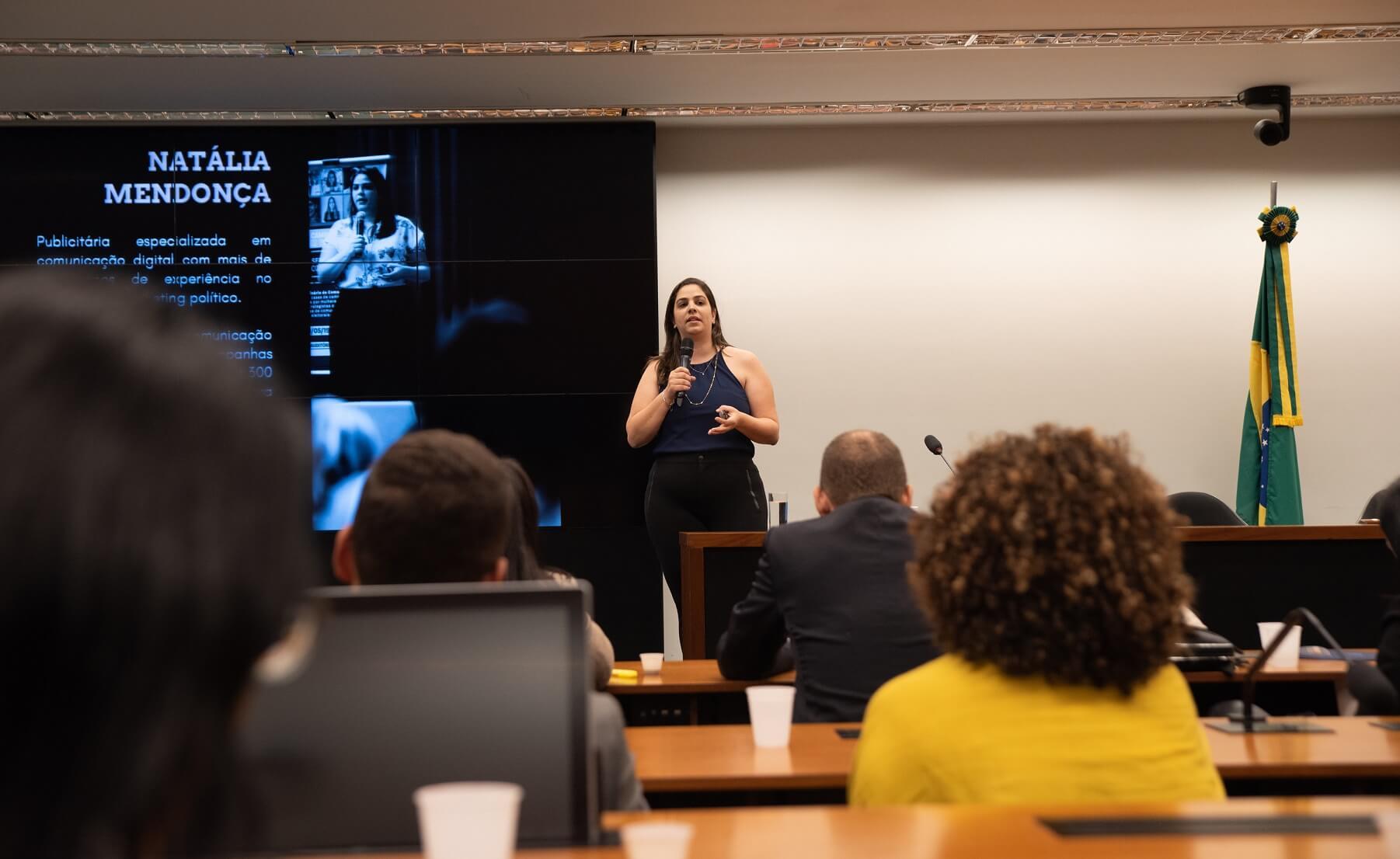 Foto da professora Natália Mendonça em palestra na Câmara dos deputados